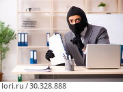 Купить «Male gangster stealing information from the office», фото № 30328888, снято 20 декабря 2018 г. (c) Elnur / Фотобанк Лори
