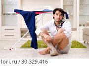 Купить «Young man ironing in the bedroom», фото № 30329416, снято 29 ноября 2018 г. (c) Elnur / Фотобанк Лори