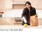 Купить «Young handsome man with vegetables in the kitchen», фото № 30329452, снято 28 ноября 2018 г. (c) Elnur / Фотобанк Лори