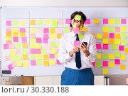 Купить «Young employee in conflicting priorities concept», фото № 30330188, снято 16 октября 2018 г. (c) Elnur / Фотобанк Лори