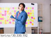 Купить «Young handsome employee with many conflicting priorities», фото № 30330192, снято 16 октября 2018 г. (c) Elnur / Фотобанк Лори