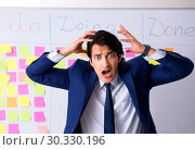 Купить «Young handsome employee in front of whiteboard with to-do list», фото № 30330196, снято 16 октября 2018 г. (c) Elnur / Фотобанк Лори