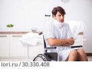 Купить «Young handsome man in wheelchair at the hospital», фото № 30330408, снято 6 сентября 2018 г. (c) Elnur / Фотобанк Лори