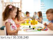 Купить «children group learning arts and crafts in playroom with interest», фото № 30338240, снято 23 марта 2019 г. (c) Оксана Кузьмина / Фотобанк Лори