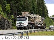 Купить «Sisu semi trailer of Telamurska Oy transports Metso Lokotrack crusher on scenic road. The machinery weighs 100000 kg. Salo, Finland - June 30, 2018.», фото № 30339792, снято 30 июня 2018 г. (c) age Fotostock / Фотобанк Лори