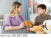 Купить «Young woman and son chatting at table with tea indoors», фото № 30347256, снято 9 февраля 2019 г. (c) Яков Филимонов / Фотобанк Лори