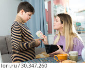 Купить «Portrait of young woman giving money to son, chatting at table», фото № 30347260, снято 9 февраля 2019 г. (c) Яков Филимонов / Фотобанк Лори