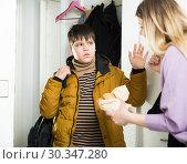Купить «Portrait of young mother and son in jacket standing near door», фото № 30347280, снято 9 февраля 2019 г. (c) Яков Филимонов / Фотобанк Лори