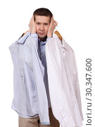 the man holds a coat hanger with a shirt on a white background. Стоковое фото, фотограф Владимир Арсентьев / Фотобанк Лори