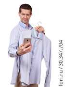 the man holds a coat hanger with a shirt and phone on a white background. Стоковое фото, фотограф Владимир Арсентьев / Фотобанк Лори