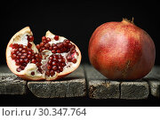 Купить «Ripe pomegranate with a half with red seeds on the edge of old rough wooden boards», фото № 30347764, снято 17 марта 2019 г. (c) Георгий Дзюра / Фотобанк Лори