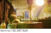Купить «Construction plant. A machine drilling a hole in the iron detail. Cooling the drill with water», видеоролик № 30347924, снято 25 февраля 2020 г. (c) Константин Шишкин / Фотобанк Лори