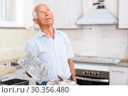 Купить «Man with plastering tools looking at repairable room», фото № 30356480, снято 19 июня 2018 г. (c) Яков Филимонов / Фотобанк Лори