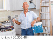 Купить «Man with plastering tools looking at repairable room», фото № 30356484, снято 19 июня 2018 г. (c) Яков Филимонов / Фотобанк Лори