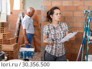 Купить «Thoughtful woman looking at list of works», фото № 30356500, снято 19 июня 2018 г. (c) Яков Филимонов / Фотобанк Лори