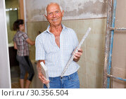 Купить «Man with woman working on apartment overhaul», фото № 30356504, снято 19 июня 2018 г. (c) Яков Филимонов / Фотобанк Лори