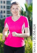 Купить «Smiling adult woman in pink T-shirt is jogging», фото № 30356624, снято 10 июня 2017 г. (c) Яков Филимонов / Фотобанк Лори