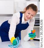 Купить «Housekeeper female 20-25 years old is cleaning dust from the desk», фото № 30356636, снято 2 июня 2020 г. (c) Яков Филимонов / Фотобанк Лори