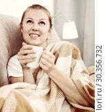 Купить «Young female is warming with tea and sitting in plaide», фото № 30356732, снято 28 января 2020 г. (c) Яков Филимонов / Фотобанк Лори