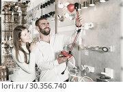 Купить «Smiling couple customers trying use modern desk lamp», фото № 30356740, снято 29 января 2018 г. (c) Яков Филимонов / Фотобанк Лори