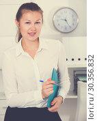 Купить «Young woman is standing with documents before signing», фото № 30356832, снято 23 августа 2019 г. (c) Яков Филимонов / Фотобанк Лори
