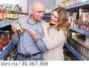 Купить «Smiling family couple choosing pickle goods in hypermarket», фото № 30367368, снято 11 апреля 2018 г. (c) Яков Филимонов / Фотобанк Лори
