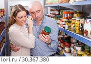 Купить «Woman and husband choosing pickle goods in supermarket», фото № 30367380, снято 11 апреля 2018 г. (c) Яков Филимонов / Фотобанк Лори