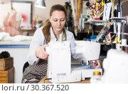 Купить «Portrait of woman designer who is working with sewing machine», фото № 30367520, снято 5 мая 2018 г. (c) Яков Филимонов / Фотобанк Лори