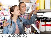 Купить «Mother and daughter holding jar with color paint», фото № 30367540, снято 12 апреля 2017 г. (c) Яков Филимонов / Фотобанк Лори