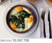 Купить «Top view of fried eggs with spinach, raisins, ham», фото № 30367708, снято 22 апреля 2019 г. (c) Яков Филимонов / Фотобанк Лори