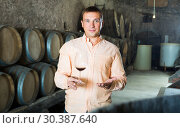 Купить «Customer holding glass of wine from wooden barrels», фото № 30387640, снято 22 сентября 2016 г. (c) Яков Филимонов / Фотобанк Лори