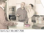 Купить «Seller shows of options for kitchen furniture», фото № 30387708, снято 4 апреля 2017 г. (c) Яков Филимонов / Фотобанк Лори