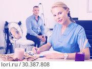 Купить «Woman specialist is writing the conclusion after procedure for man», фото № 30387808, снято 6 декабря 2019 г. (c) Яков Филимонов / Фотобанк Лори