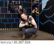 Купить «Glad girl aiming laser gun during lasertag game», фото № 30387924, снято 23 января 2019 г. (c) Яков Филимонов / Фотобанк Лори