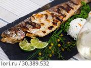 Купить «Baked whole trout with rice, served with lemon and greens at plate, glass of wine», фото № 30389532, снято 15 июня 2019 г. (c) Яков Филимонов / Фотобанк Лори