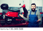 Купить «Motorcycle repair specialist shows his workplace», фото № 30389588, снято 19 апреля 2019 г. (c) Яков Филимонов / Фотобанк Лори