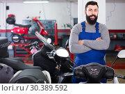 Купить «smiling man worker displaying various motorcycles in workshop», фото № 30389592, снято 21 сентября 2019 г. (c) Яков Филимонов / Фотобанк Лори