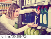 Купить «concentrated girl customer looking for cleaners for home in supermarket», фото № 30389724, снято 23 ноября 2016 г. (c) Яков Филимонов / Фотобанк Лори
