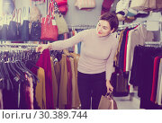 Купить «Purchaser decide on stylish clothes», фото № 30389744, снято 7 февраля 2017 г. (c) Яков Филимонов / Фотобанк Лори