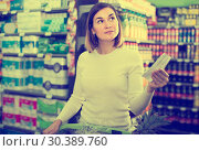 Купить «woman customer looking at notes in shopping list», фото № 30389760, снято 23 ноября 2016 г. (c) Яков Филимонов / Фотобанк Лори