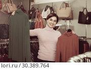 Купить «Female shopper examining turtleneck sweaters in women's cloths shop», фото № 30389764, снято 7 февраля 2017 г. (c) Яков Филимонов / Фотобанк Лори