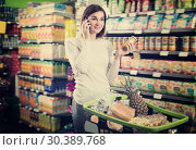 Купить «Cheerful female talking on phone about shopping», фото № 30389768, снято 23 ноября 2016 г. (c) Яков Филимонов / Фотобанк Лори