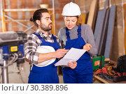 Купить «Worker man is clarifying details of work from foreman», фото № 30389896, снято 6 марта 2019 г. (c) Яков Филимонов / Фотобанк Лори