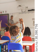 Купить «Rear view of school kids raising hand to answer at a question», фото № 30390716, снято 17 ноября 2018 г. (c) Wavebreak Media / Фотобанк Лори