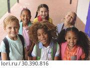 Купить «Happy school kids standing in corridor», фото № 30390816, снято 17 ноября 2018 г. (c) Wavebreak Media / Фотобанк Лори