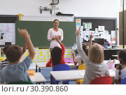 Купить «School kids raising hand while they are sitting on their chair », фото № 30390860, снято 17 ноября 2018 г. (c) Wavebreak Media / Фотобанк Лори