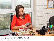 Девушка в офисе считает деньги, сидя за столом. Стоковое фото, фотограф Иванов Алексей / Фотобанк Лори