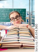 Купить «Female student with many books sitting in the classroom», фото № 30414960, снято 19 ноября 2018 г. (c) Elnur / Фотобанк Лори