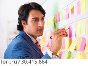 Купить «Young handsome employee with many conflicting priorities», фото № 30415864, снято 16 октября 2018 г. (c) Elnur / Фотобанк Лори