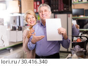 Купить «Mature couple buying on credit agreement for home appliances», фото № 30416340, снято 21 ноября 2019 г. (c) Яков Филимонов / Фотобанк Лори